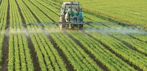 трактор вносит в поле пестициды